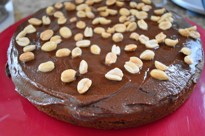The bottom layer of the decadent chocolate peanut butter cake, frosted on top with the peanuts sprinkled.