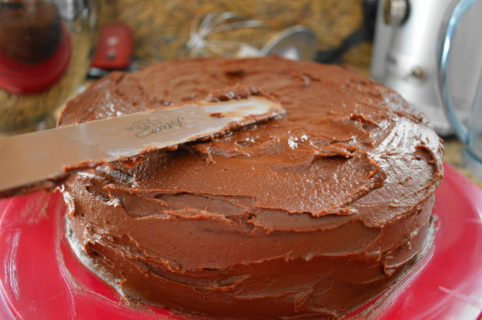 Finishing up frosting the decadent chocolate peanut butter cake!