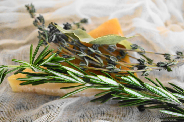 """The key to flavor in my gravy is what I affectionately call the """"package of deliciousness"""". I cut the rind off of the parmesan wedge I was using and wrapped it up in cheesecloth with thyme, bay leaves, rosemary and peppercorns."""