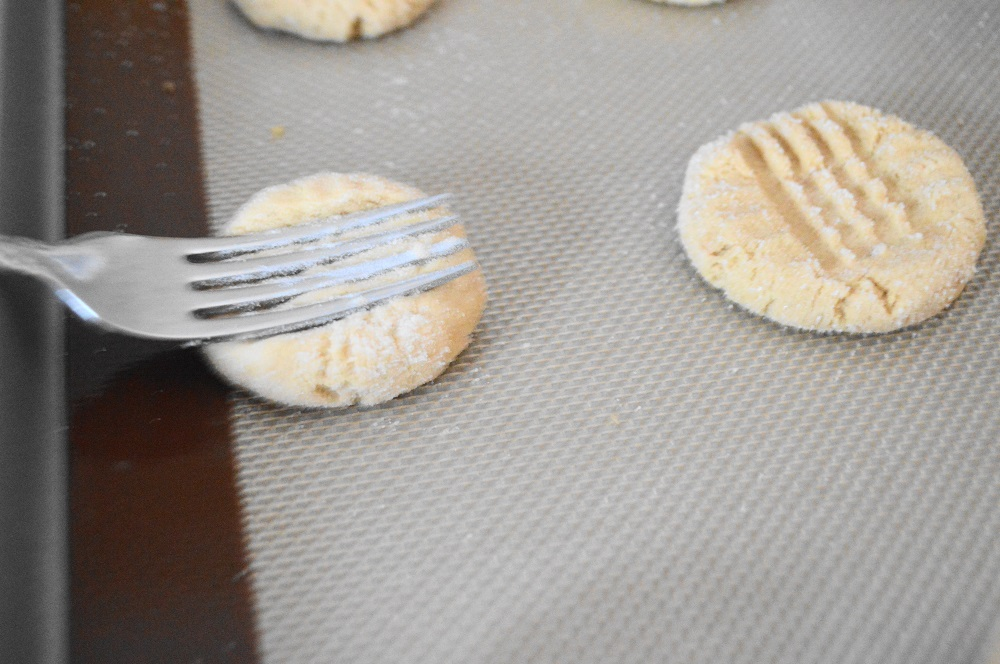 I used my cookie scoop to get perfect portions of the dough. I rolled them into balls and coated them in sugar. The final touch was to use a fork to give the peanut butter cookies their signature criss cross marks. I just gently pressed down the center vertically and then horizontally.
