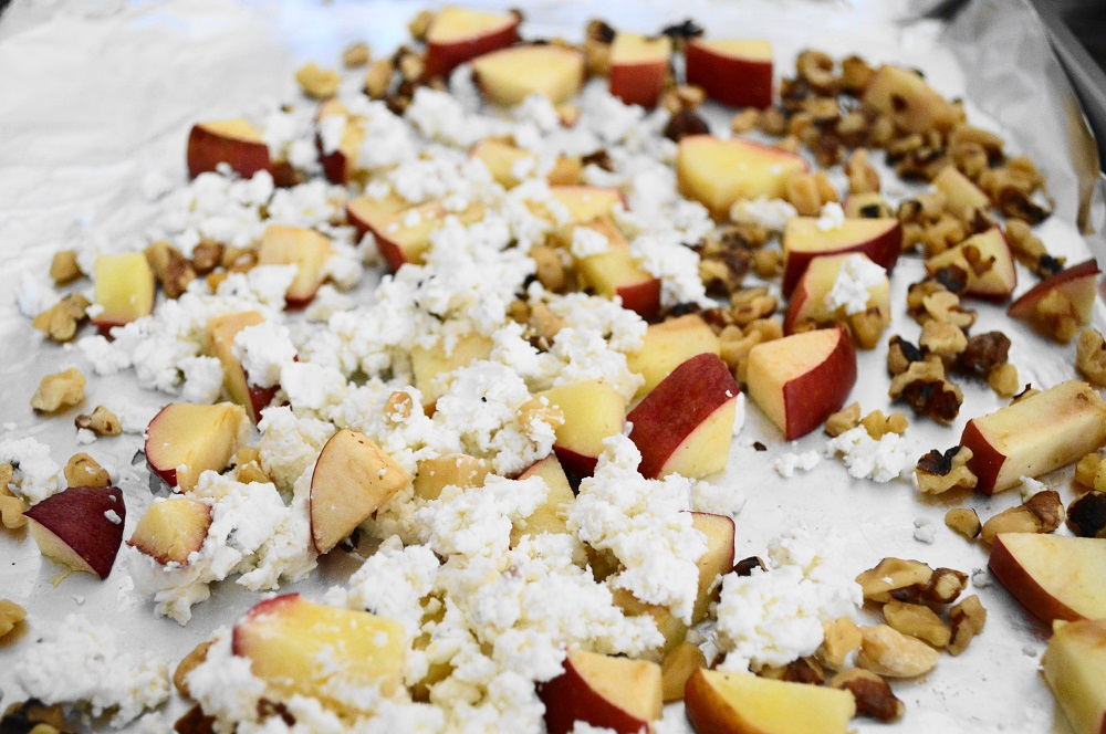 First, I spread my diced apple and chopped walnuts out on a lined sheet tray. I wanted them to just get toasty for about 5 minutes in the oven. When the tray came out, I let it cool for a minute before I crumbled the goat cheese on it. That allowed the goat cheese to warm up without melting!