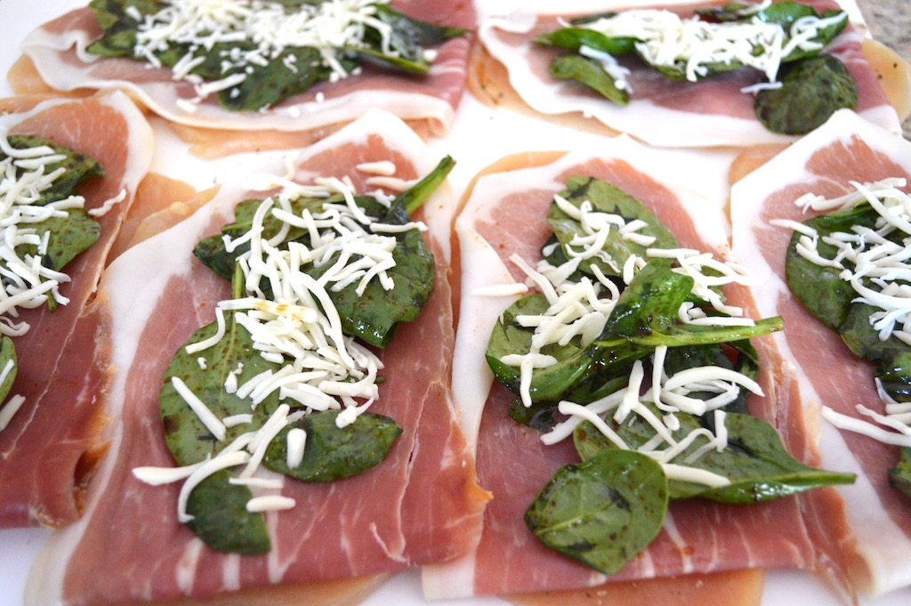 Then it was time to put together the chicken saltimbocca. I layered a paper thin slice of prosciutto onto each of my chicken breasts. The dressed spinach and shredded mozzarella cheese went on top. Then I just rolled each of them up tight like a jelly roll and secured them with toothpicks!