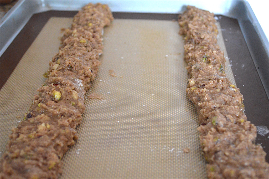 The thing about this hazelnut pistachio biscotti dough was that it was really sticky. So I made sure to have my surfaces and hands floured when I worked with it. I divided it in half and formed each half into logs that went almost the length of my sheet pan. Then I lightly pressed down on the logs to make the side on the tray flat. That formed the signature biscotti half moon shape before they baked!