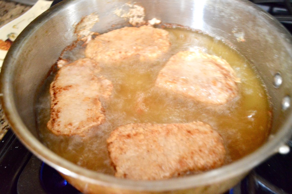 Dredging the smokey maple glazed pork chops through seasoned flour ...